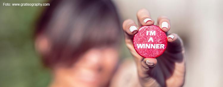 Frau hält Button mit Aufschrift I'm a Winner in der Hand